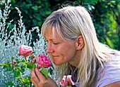 Woman sniffs at Rosa (Rose)