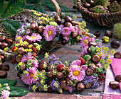 Autumn wreath with asters, chestnuts and fruits