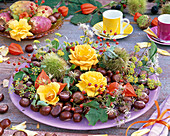 Autumn decoration with roses, berries and fruits
