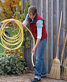Gardening equipment, woman let's water out from garden hose