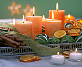 Orange candles, citrus and cinnamon sticks on tray