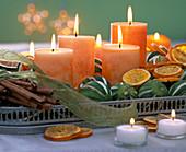Orange candles, citrus and cinnamon sticks on tray