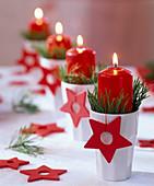 Adventskranz mit Pinus (Kiefer) in weißen Bechern mit roten Kerzen und Sternen