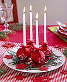 Advent wreath of red Christmas tree balls with star motifs and white candles