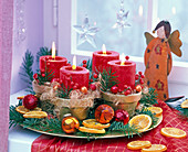 Advent wreath with red candles and pseudotsuga, citrus