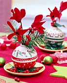 Cyclamen in Christmas tree balls with Nordic motifs as a vase