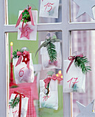 Advent calendar made of transparent paper bags with small gifts