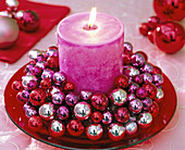 Candle wreath of small Christmas tree balls with pink pillar candle