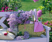 Syringa in wicker bag with bottles, bread, towel on white bench