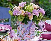 Strauß aus Rosa (Rosen), Freesia (Freesien), Viburnum (Schneeball) in Papiertüte