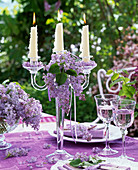 Glass candle holder decorated with syringa, drinking glasses, table settings