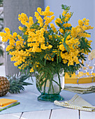 Bouquet of Acacia dealbata in glass vase, checkered napkin, books