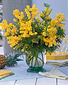 Strauß aus Acacia dealbata (Mimosen) in Glasvase, karierte Serviette, Bücher