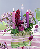 Syringa in small bottles with wreaths of grass as a candle holder