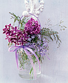 Small bouquet of different Syringa, and grasses in handle glass