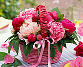 Paeonia in wicker basket with ribbon on checkered tablecloth