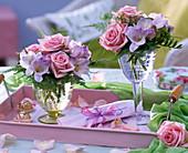 Kleine Sträuße aus Rosa (Rosen), Freesia (Freesien) und Asparagus