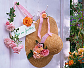 Rose on hook and straw hat, sign 'Am in the garden'