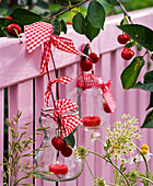 Lanterns with Prunus (cherry) with checkered ribbons on fence
