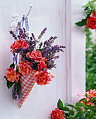 Bouquet of pink and lavandula in checkered bag on hook