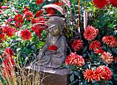 Buddha figure between Dahlia and Pennisetum 'Rubrum'
