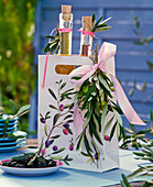 Bottles with herb oils in paper bag with olea and olives