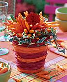 Arrangement of ornamental paprika in cachepot from bast