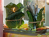 Lantern and cutlery glass wrapped with Brassica leaves