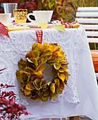Prunus autumn foliage wreath on the side of a laid table