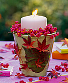 Candle decoration with Euonymus and autumn leaves from Acer