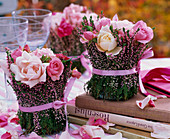 Small bouquets of roses in vase wrapped with Calluna