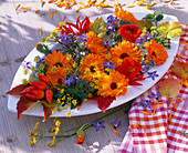 Table decoration with herbs, calendula, foeniculum