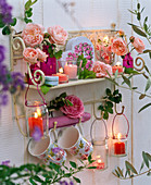 Wall shelf decorated with pink, cups, lanterns, box of roses