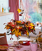 Hanging wreath with autumn leaves of liquidambar, rosehips and berries