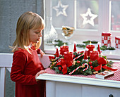 Girl admires Advent wreath with Juniperus (Juniper), Abies
