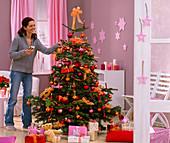Frau entzündet Kerzen an Abies nordmanniana (Nordmanntanne) als Weihnachtsbaum