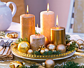 Advent wreath in gold with Christmas tree decorations and Abies branches