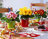 Carnival table decoration with primula, streamers, fritters