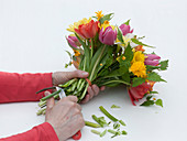 Tying a colorful spring bouquet