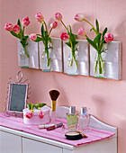 Tulipa in small bottles hanging on the bathroom wall, dressing table