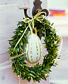 Buxus wreath with ostrich egg and text 'Frohe Ostern' at the door