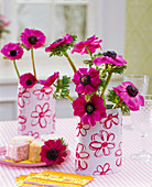 Bouquet of anemone coronaria in cans with floral motifs