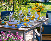 Table decoration with white easter bunnies in pots with Carex, bouquet