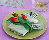 Napkin decoration with tulipa on checkered folded napkin