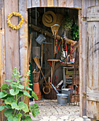 View through open door into the tool house with tools, wheelbarrow, pots