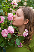 Woman sniffs at Rosa 'Gertrude Jekyll' (English fragrance rose)