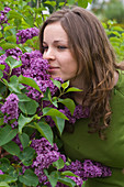 Woman sniffs at Syringa 'memory of Ludwig Späth' (lilac)