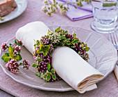 Napkin ring made of different origanum around white napkin