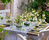 Table decoration with daisies in small bottles