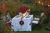 Gedeckter Tisch vor Herbstbeet mit Miscanthus (Chinaschilf) abends